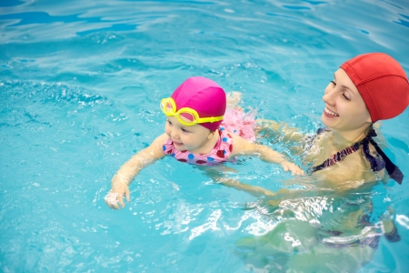 swimming pool float: One year  baby girl at his first swimming lesson with mother Stock Photo