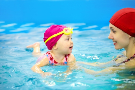 Ett år flicka på sin första simning lektion med mamma