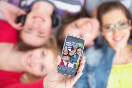 school teens: group of teenage friends take photo on cell phone