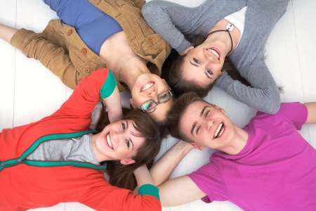secondary education: group of teenage friends look up at the camera with bright smiles