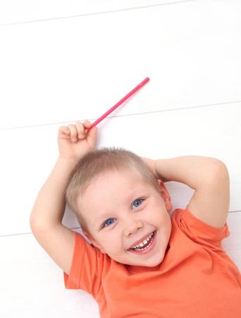 Portret van grappige kleine jongen liggend op de vloer