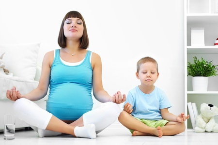 pregnancy yoga: Pregnant woman with her first son is engaged in fitness Stock Photo
