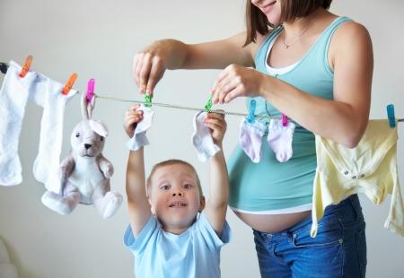 hijos: Niño pequeño que ayuda a colgar ropa a su madre embarazada