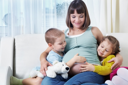 Portrait of happy pregnant woman with her two children together