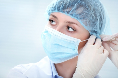 therapeutist: Face of nurse in sterile mask looking at camera