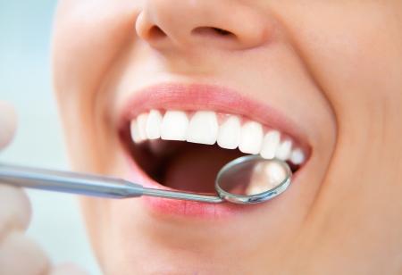 odontologia: Primer plano de mujer joven que tiene los dientes recurrido al examen