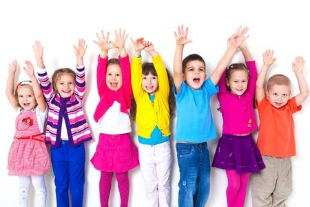 trẻ em: nhóm lớn các trẻ em vui vẻ kéo tay lên bức tường trắng