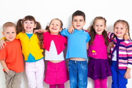 elementary age girl: Big  group of diverse children  at  white wall
