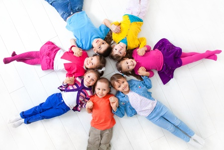 Seven kids are on the floor together  Top view photo