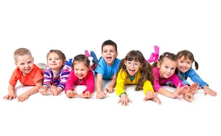 Groep van zeven speelse kinderen liggen op de vloer samen