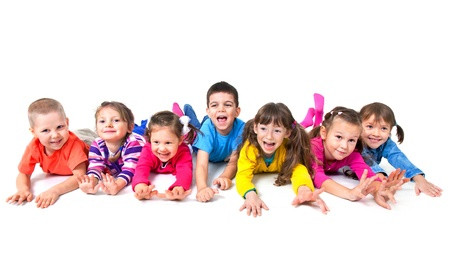 Group of seven  playful children are lying on floor  together