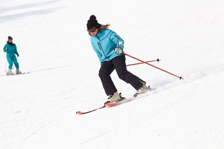 moving down: Female skier turning in deep powder with mountains valleys Stock Photo