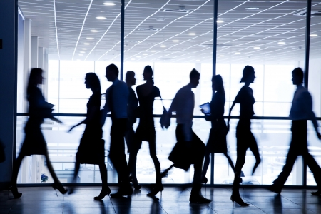 silhouettes of business people rushing for the large windows in the background Stock Photo - 18356513