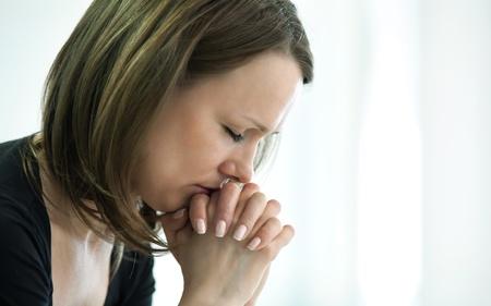 traurige junge Frau gekreuzten Fingern f�r ihr Gesicht in der Krise Moment Lizenzfreie Bilder