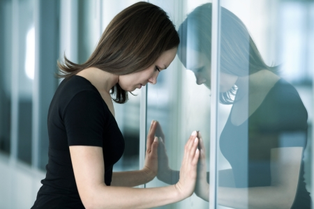jonge vrouw leunde tegen glazen wand in crisis ogenblik Stockfoto