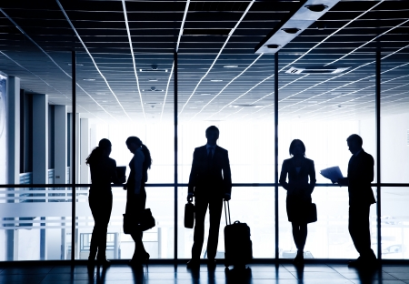 Several silhouettes of businesspeople interacting  background airport photo