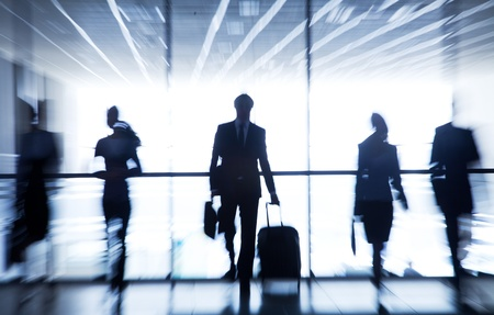 business transaction: Several silhouettes of businesspeople interacting  background airport