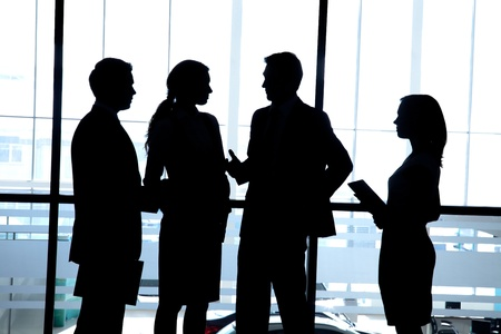 Several silhouettes of businesspeople interacting  background business centre Stock Photo - 18356504