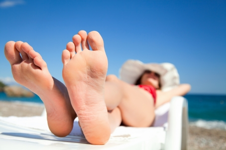 sunbathe: Young woman relaxing in chaise longue on the beach Stock Photo