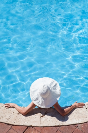 Unrecognizable woman in big hat relaxing on the swimming pool Stock Photo