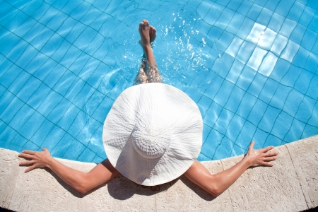 Unrecognizable woman in big hat relaxing on the swimming pool photo