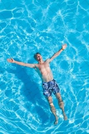 Positive man enjoying in the swimming pool