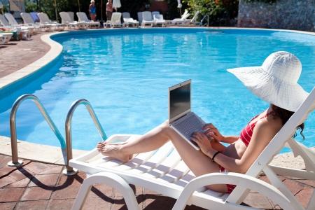 бассейн: Молодая женщина в большой шляпе, расслабляющий возле бассейна с ноутбуком