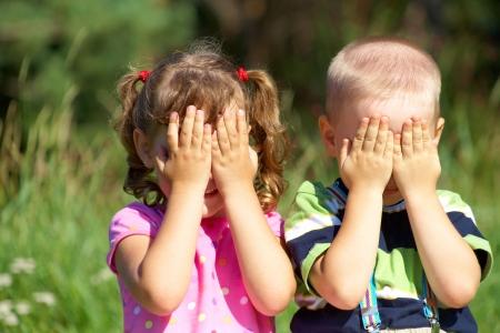 hermanos jugando: Dos ni�os divertidos est�n jugando, cubri�ndose la cara con las manos