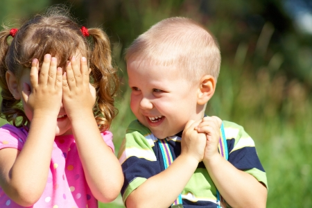 Two funny kids are playing, covering his face with his hands Stock Photo