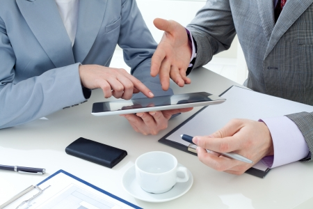 financial leadership: Irreconocible colegas de negocios trabajando juntos y utilizando una tableta digital