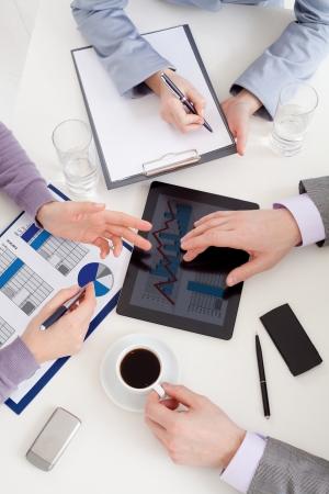 working together: Unrecognizable business colleagues working together and using a digital tablet Stock Photo