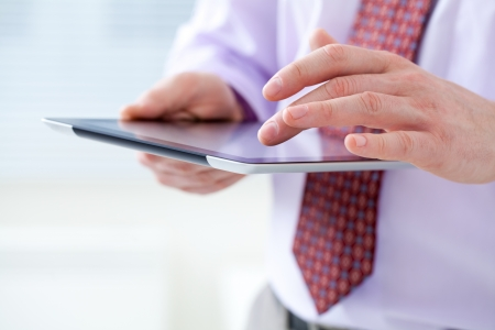 Unrecognizable business man holding a digital tablet photo