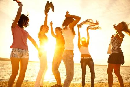 playa: adolescentes jóvenes felices bailando en la playa en la hermosa puesta de sol del verano