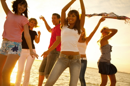 company party: happy young teens dancing at the beach on  beautiful summer sunset