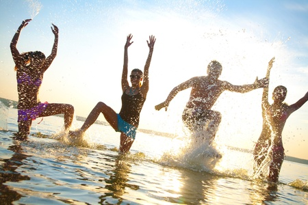 group of happy young people dancing and spraying at the beach on  beautiful summer sunset Stock Photo