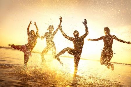 행복 한 젊은 사람들의 그룹은 춤과 아름 다운 여름 일몰 해변에서 분사