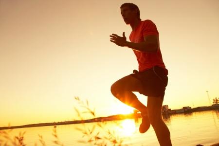 hombre deportista: Hombre joven que se ejecuta a lo largo de la orilla del mar al atardecer