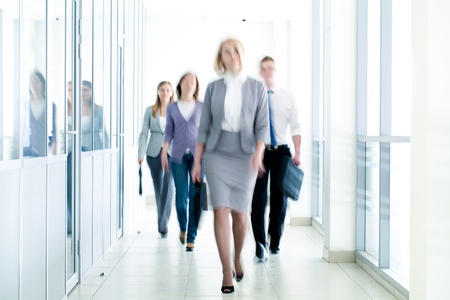 businesslike: businesspeople walking in the corridor of an business center, pronounced motion blur