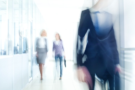 hallway: businesspeople walking in the corridor of an business center, pronounced motion blur