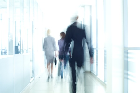 BUSY OFFICE: businesspeople walking in the corridor of an business center, pronounced motion blur