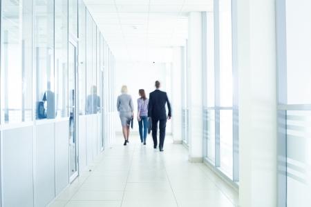 personas caminando: empresarios caminando por el pasillo de, un centro de negocios desenfoque de movimiento pronunciado