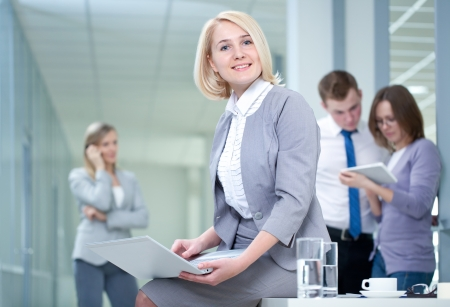 confident consultant: Successful woman with digital tablet and colleagues in the background