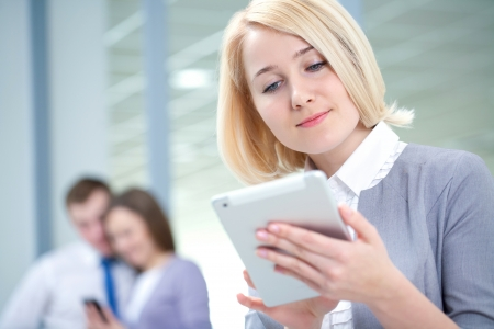 Successful woman with digital tablet and colleagues in the background photo