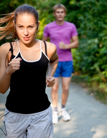 couple exercising: Young couple jogging on a morning park Stock Photo