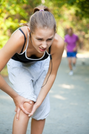 A female jogger with sudden knee-pain photo