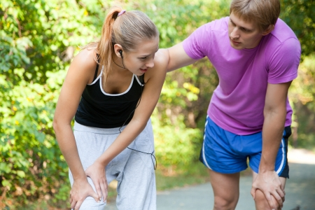 cramp: A female jogger with sudden knee-pain Stock Photo