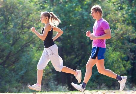 ジョグ: 若いカップルの朝公園でジョギング