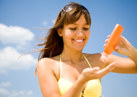smear: beautiful young woman in bikini smear protective cream on the skin on the beach under the sun Stock Photo