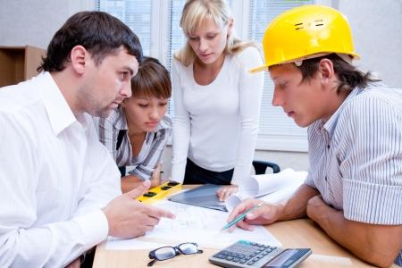 contrato de trabajo: Reuni?n del equipo de ingenieros trabajando en un proyecto de construcci?n en la mesa