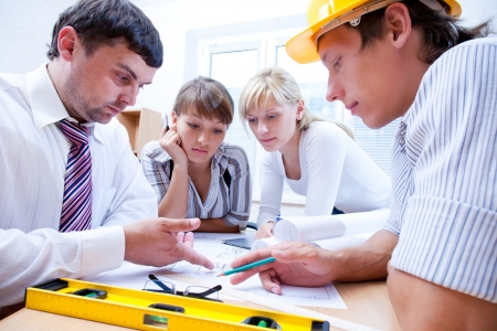 employees group: Meeting the team of engineers working on a construction project at the table Stock Photo